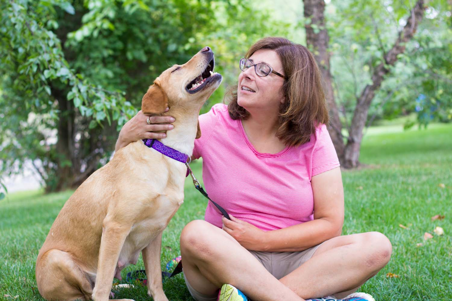Woman sitting in grass with happy dog