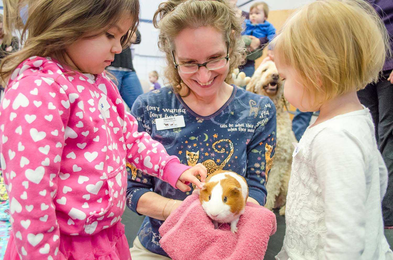 Two children and adult woman petting guinea pig