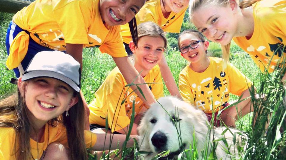Six kids attending AHS Youth Camp, petting white dog