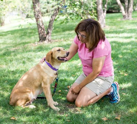 A woman sitting in the grass petting a yellow lab